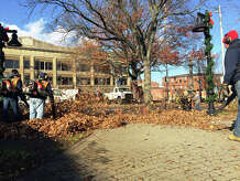 City workers clear library plaza and string trees with lights in preparation for the annual Light the Lights celebration.