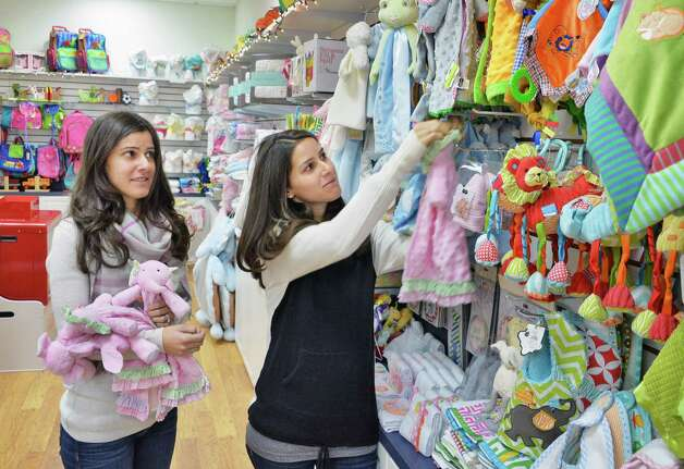Twin sisters and co owners Jodi Emmott, left, and Heather Kruse stock shelves at their Clearly Yours store in Newton Plaza Thursday Nov. 20, 2014, in Colonie, NY.  (John Carl D'Annibale / Times Union) Photo: John Carl D'Annibale / 00029556A