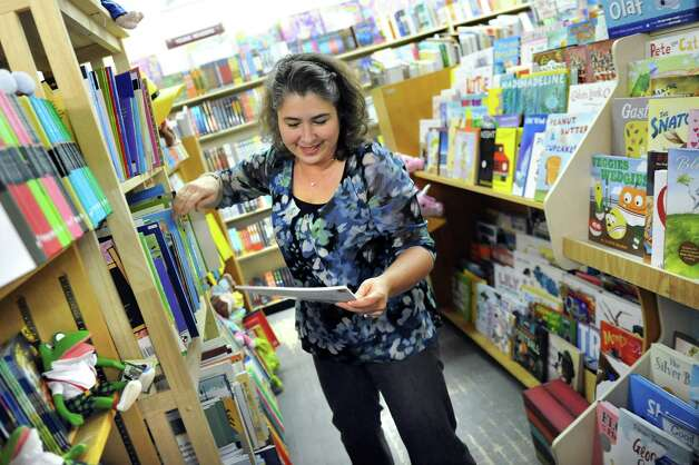 Employee Amy Humphrey finds a children's book for a customer on Tuesday, Nov. 25, 2014, at I Love Books in Delmar, N.Y. (Cindy Schultz / Times Union) Photo: Cindy Schultz / 00029619A