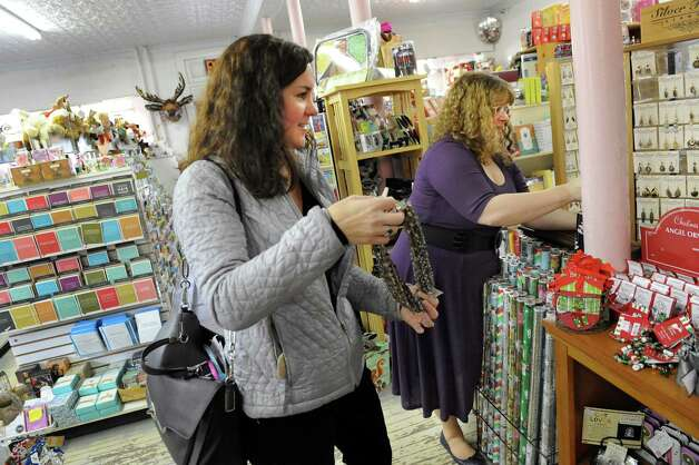 Shop owner Melissa Steen, right, assists Necole Good of Albany as she shops for holiday gifts on Tuesday, Nov. 25, 2014, at I Love Books in Delmar, N.Y. (Cindy Schultz / Times Union) Photo: Cindy Schultz / 00029619A