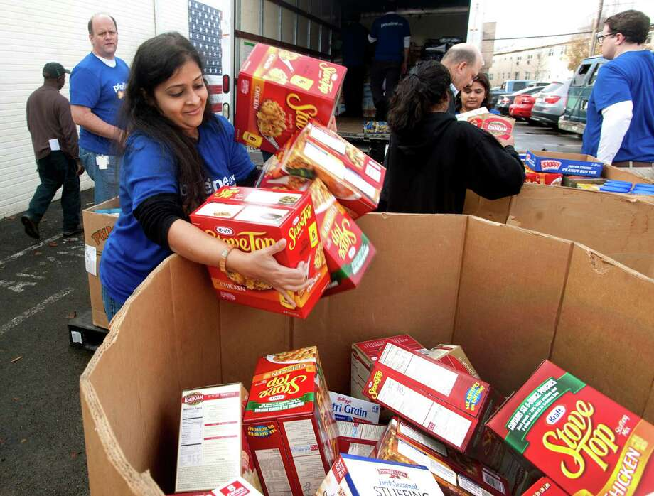 Zainab Tohfafarosh, a Priceline Group employee, unloads an armful of Stove Top stuffing into a box at the CT Food Bank located at 461 Glenbrook Road, Stamford, Conn. on Monday, Nov. 24, 2014. Priceline.com and Kayak raised $30,503 for the Food Bank, which translated into 14,158 pounds of food, including 464 turkeys. Photo: Cathy Zuraw / Stamford Advocate