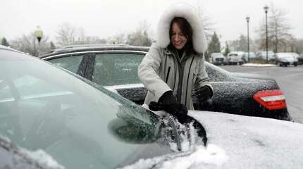 Kathie Koether, of Fairfield, cleans snow off of her windshield as she leaves work in Trumbull, Conn., Wednesday, Nov. 26, 2014, under snowy skies.