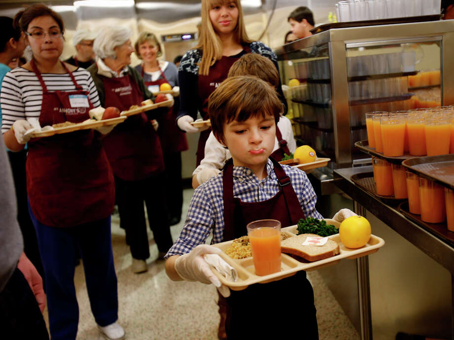 Thomas Vos, a grandson of Rep. Nancy Pelosi, serves meals at St. Anthony's dining room in S.F. Photo: Brant Ward / The Chronicle / ONLINE_YES