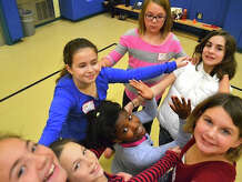 Students from fifth and sixth grade classes at Newtownís Reed Intermediate School rehearse movement techniques under the guidance of Pilobolus dancers.The students will perform Friday, Dec. 19, in Newtown. Members of the dance troupe will perform a duet.