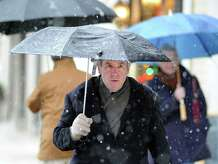 A frosting of snow covers the top of the umbrella of Carl Carlson of Greenwich as he was walking on Greenwich Avenue during the first winter storm of the season in Greenwich, Conn., Wednesday, Nov. 26, 2014. The National Weather Service is forecasting a twenty percent chance of snow showers between 10 a.m. and 2 p.m. on Thanksgiving.