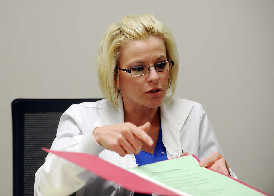 Katie Powell, a patient care navigator, talks about the health diaries the Smart Health Clinic gives to patients with chronic diseases. Patient care navigators at the Smart Health Clinic of Baptist Hospitals of Southeast Texas assist patients with chronic diseases through the healthcare process, including health education and decision-making.  Photo taken Wednesday 11/19/14  Jake Daniels/The Enterprise Photo: Jake Daniels / ©2014 The Beaumont Enterprise/Jake Daniels
