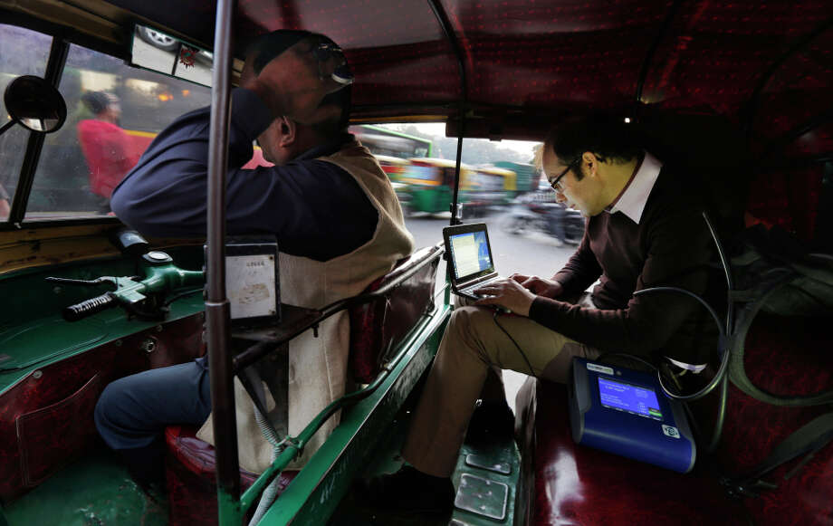 Scientist Joshua Apte monitors pollution levels on his laptop as he travels in an auto- rickshaw during rush-hour traffic in New Delhi. Photo: Altaf Qadri / Associated Press / AP