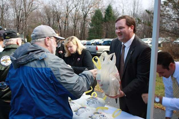 Tully Rinckey PLLC Founding Partner Mathew B. Tully, right, hands a turkey to a veteran at the annual Turkeys for Veterans event in partnership with Hannaford Supermarkets at the law firm?s New Karner Road office on Monday, November 24. About 170 turkeys were provided to Capital Region military personnel and veterans. In the background is Hannaford Supermarkets Community Relations Specialist Amy White.
