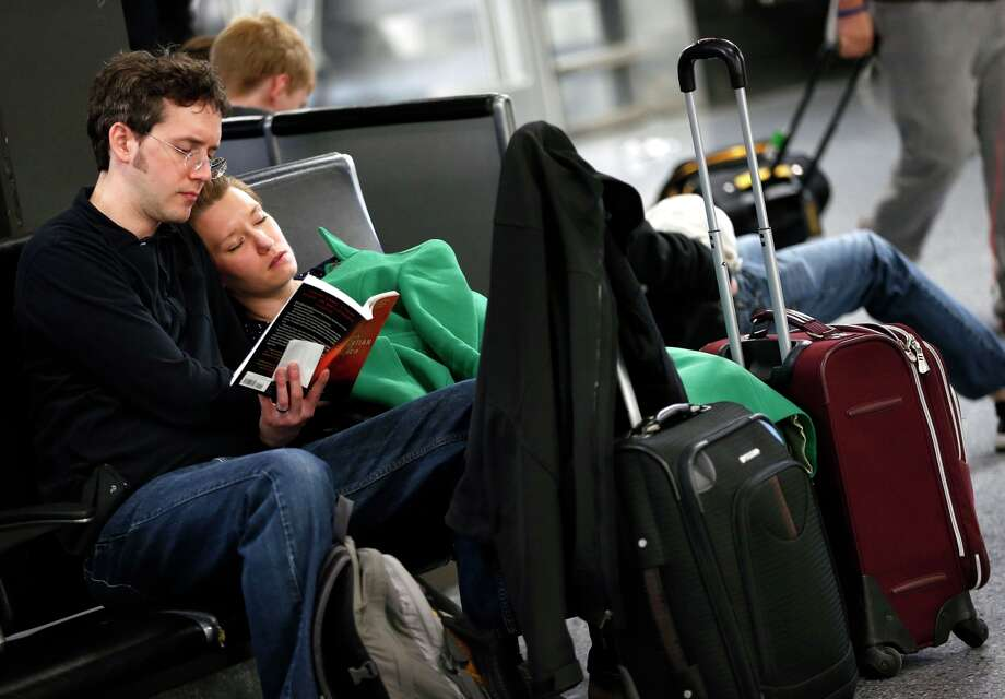 Matthew Nickel (left) and wife Autumn, who flew in from Baltimore, wait at Logan International Airport in Boston for his mother, whose flight was delayed. Photo: Michael Dwyer / Associated Press / AP