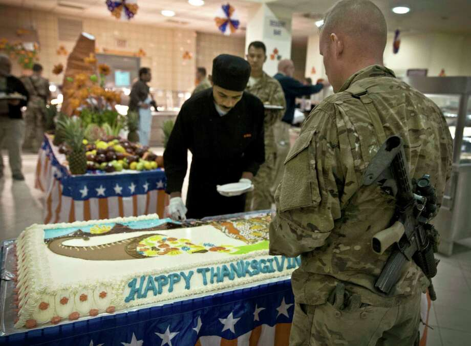 A U.S. soldier waits to get a piece of the Thanksgiving cake in Kabul, Afghanistan, last year. Our soldiers help preserve many of the blessings were celebrate today. Photo: Anja Niedringhaus / Associated Press File Photo / AP