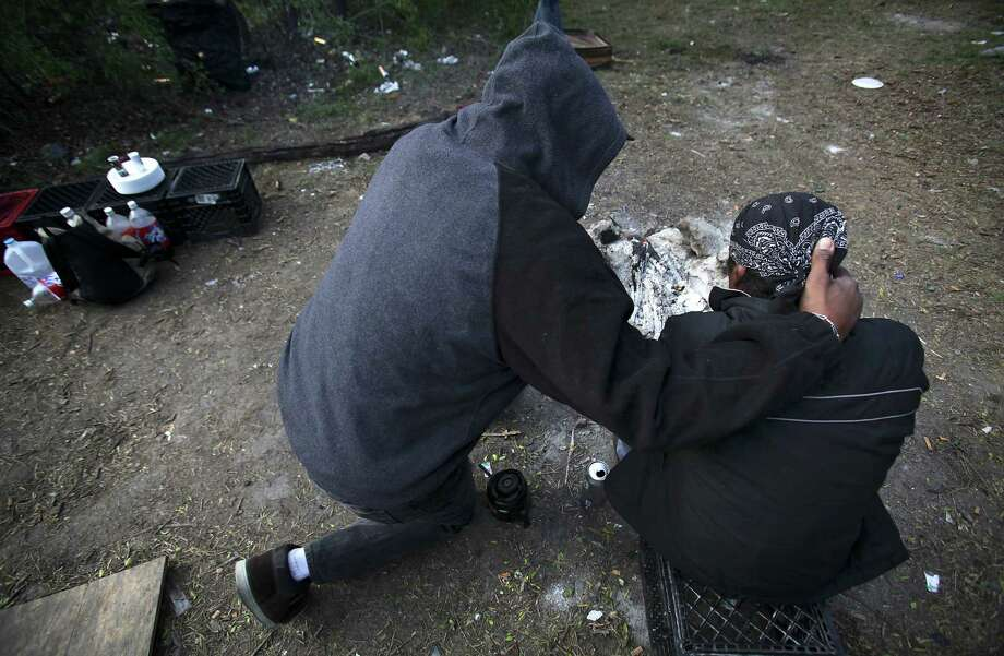 In this file photo, Ron Brown, left, Prospect Courtyard Liaison at Haven for Hope, comforts a homeless man with prayer when he began crying as he sat by his campfire, near Goliad Rd. and SE Military Dr. Photo: BOB OWEN / BOB OWEN / SAN ANTONIO EXPRESS-NEWS / rowen@express-news.net