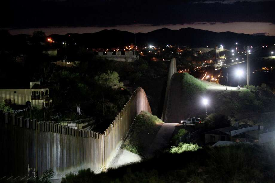 The border wall is illuminated at night in Nogales, Arizona. Readers maintain that there is no comparison between that border wall and the Berlin Wall, a comparison suggested by a previous letter writer. Photo: Sandy Huffaker / Sandy Huffaker / Getty Images / 2012 Getty Images
