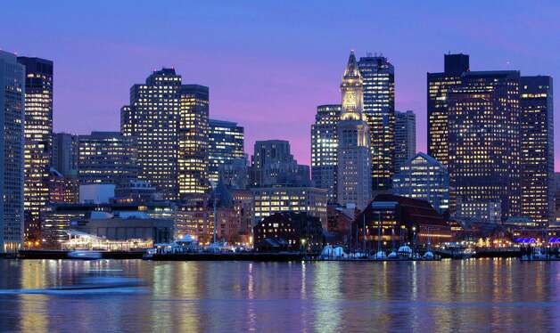 FILE - In this Jan. 6, 2012 file photo, the Boston city skyline is illuminated at dusk as it reflects off the waters of Boston Harbor. The city is bidding on the 2024 Summer Olympics, and the crux of the proposal is a walkable, sustainable, technology-based event that would harness the resources of the area's 100 colleges and universities to keep the Games affordable and compact. (AP Photo/Michael Dwyer, File) ORG XMIT: BX401 Photo: Michael Dwyer / AP