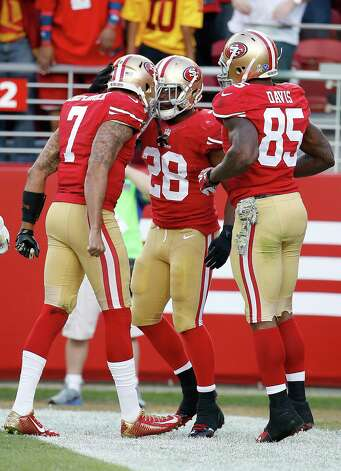 San Francisco 49ers running back Carlos Hyde, right, celebrates with quarterback Colin Kaepernick (7) and tight end Vernon Davis (85) after running for a 4-yard touchdown against the Washington Redskins during the fourth quarter of an NFL football game in Santa Clara, Calif., Sunday, Nov. 23, 2014. (AP Photo/Tony Avelar) ORG XMIT: FXN126 Photo: Tony Avelar / FR155217 AP