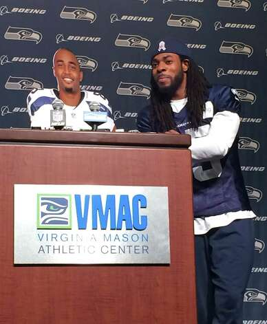 Seattle Seahawks cornerback Richard Sherman, right, stands beside a cardboard cutout of wide receiver Doug Baldwin, at podium, while speaking at the Seahawks headquarters Tuesday, Nov.25, 2014, in Renton, Wash. Baldwin himself was hiding behind the cardboard cutout. The pair put together a routine that took digs at the NFL after teammate Marshawn Lynch was fined $100,000 by the league last week for not speaking to the media. (AP Photo/Tim Booth)   ORG XMIT: FX112 Photo: Tim Booth / AP