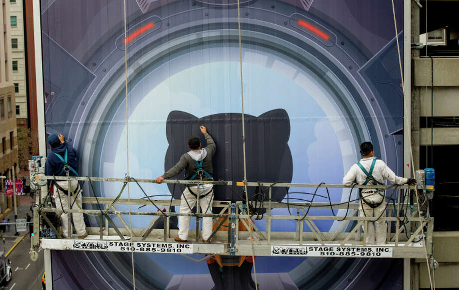 Workers install an S.F. billboard for GitHub, one of the companies vying for attention — and workers. Photo: David Paul Morris / Bloomberg / © 2014 Bloomberg Finance LP