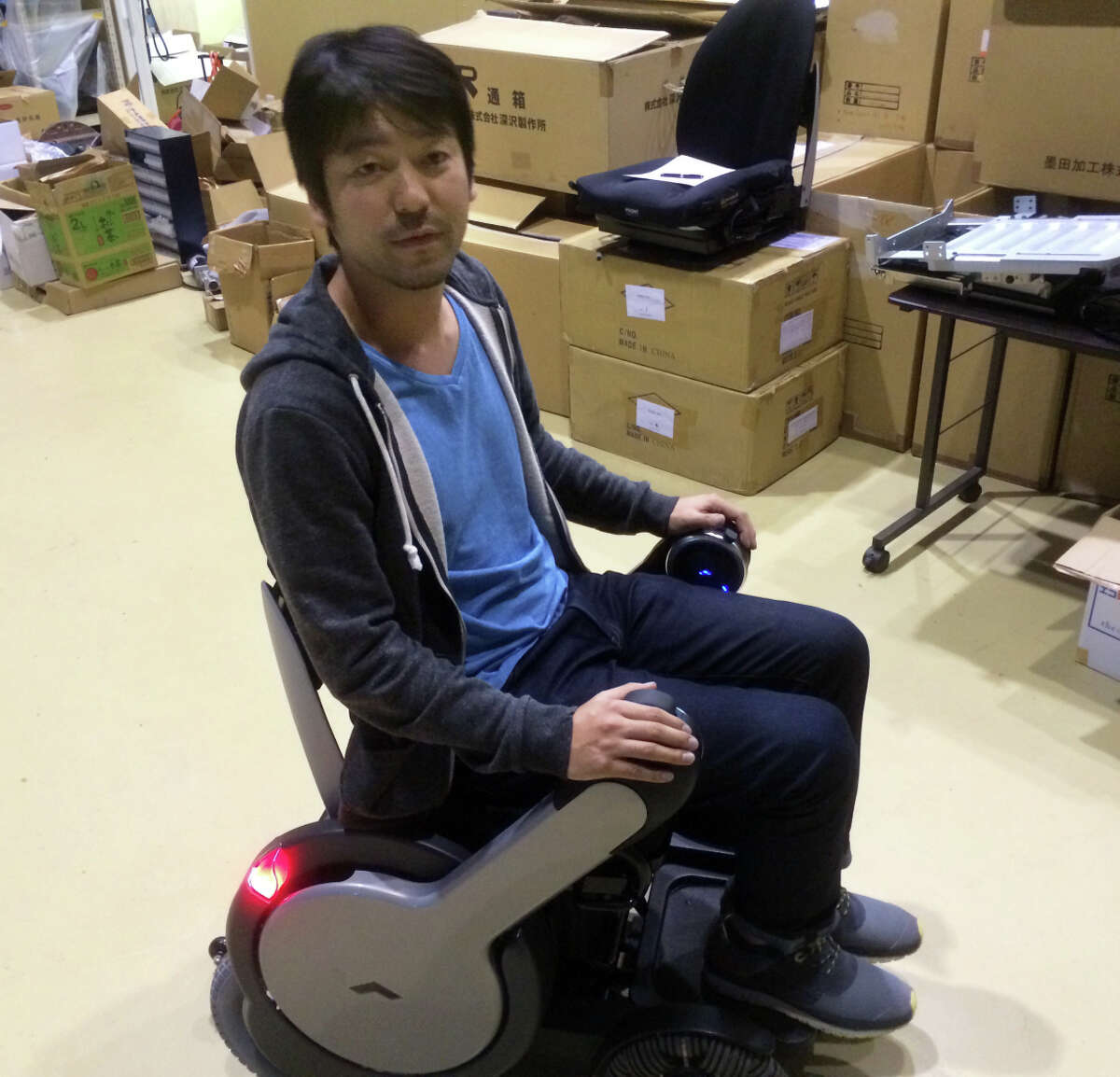 """Satoshi Sugie, CEO of Whill, shows off his startup's electric """"personal mobility device"""" - an advanced wheelchair that can be controlled with a smartphone app and has treads capable of handling almost any level terrain."""