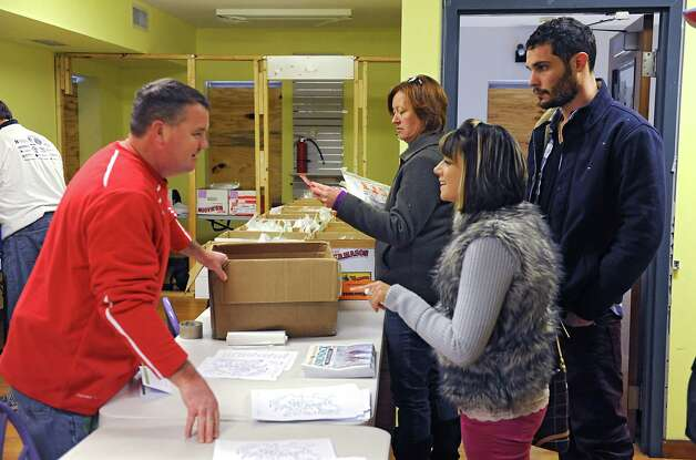 From left, volunteer Leonard Bacon helps Pam Lyons of Burnt Hills, Molly Lemme of Colonie and her boyfriend Ethan Boatright of Rhode Island as they arrive to pick up their packets for the Ellis Medicine's Cardiac Classic 5K in Schenectady Central Park on Wednesday, Nov. 26, 2014 in Schenectady, N.Y. The 5K Road Race, Wellness Walk, and Fun Run which happens on Thanksgiving Day draws more than 1,700 runners and walkers each year and supports Ellis Medicine's Wright Heart Center. (Lori Van Buren / Times Union) Photo: Lori Van Buren / 00029602A