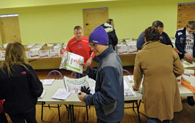Runners and walkers are given their packets from volunteers at the Ellis Medicine's Cardiac Classic 5K packet pickup in Schenectady Central Park on Wednesday, Nov. 26, 2014 in Schenectady, N.Y. The 5K Road Race, Wellness Walk, and Fun Run which happens on Thanksgiving Day draws more than 1,700 runners and walkers each year and supports Ellis Medicine's Wright Heart Center. (Lori Van Buren / Times Union) Photo: Lori Van Buren / 00029602A