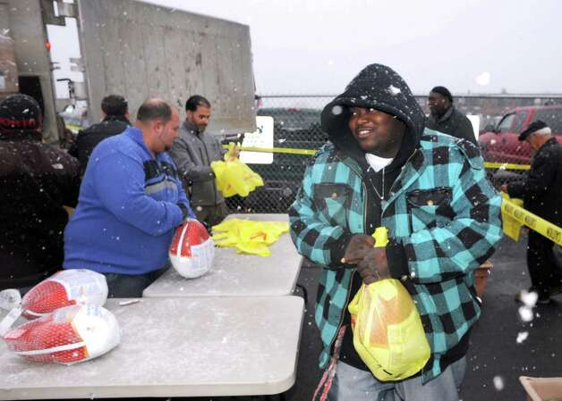 Lewis Watkins of Albany is all smiles as he receives a turkey as R.J. Valente Gravel, Inc employees handed out 800 Thanksgiving turkeys at the Central Avenue OTB on  Wednesday Nov. 26, 2014 in Albany, N.Y. (Michael P. Farrell/Times Union) Photo: Michael P. Farrell / 00029606A