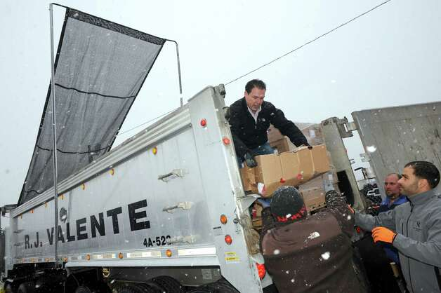 Anthony Valente off loads a tractor trailer with 800 Thanksgiving turkeys that R.J. Valente Gravel, Inc gave away at the Central Avenue OTB on  Wednesday Nov. 26, 2014 in Albany, N.Y. (Michael P. Farrell/Times Union) Photo: Michael P. Farrell / 00029606A