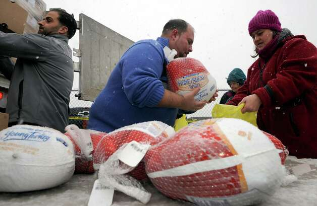 R.J. Valente Gravel, Inc employees hand out 800 Thanksgiving turkeys at the Central Avenue OTB on  Wednesday Nov. 26, 2014 in Albany, N.Y. (Michael P. Farrell/Times Union) Photo: Michael P. Farrell / 00029606A