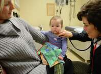 Pediatrician, Dr. Diane Tenenbaum, right, examines one-year-old London Atkins who is held by her mother Laura Atkins, left, Friday morning, Nov. 14, 2014, at St. Peter's Children's Health Center on Madison Ave. in Albany, N.Y. (Will Waldron/Times Union)