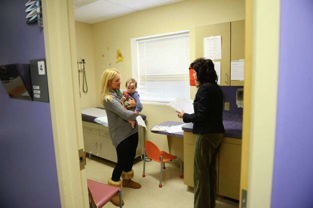 Laura Atkins, left, takes daughter London Atkins, 1, to see Dr. Diane Tenenbaum, right, for pediatric exam Friday morning, Nov. 14, 2014, at St. Peter's Children's Health Center on Madison Ave. in Albany, N.Y. (Will Waldron/Times Union) Photo: WW / 00029486A