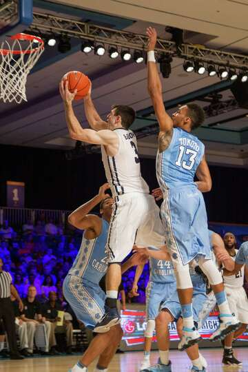 Butler's Alexander Barlow (3), goes up for a shot against UNC's J.P. Tokoto (13) during their game i
