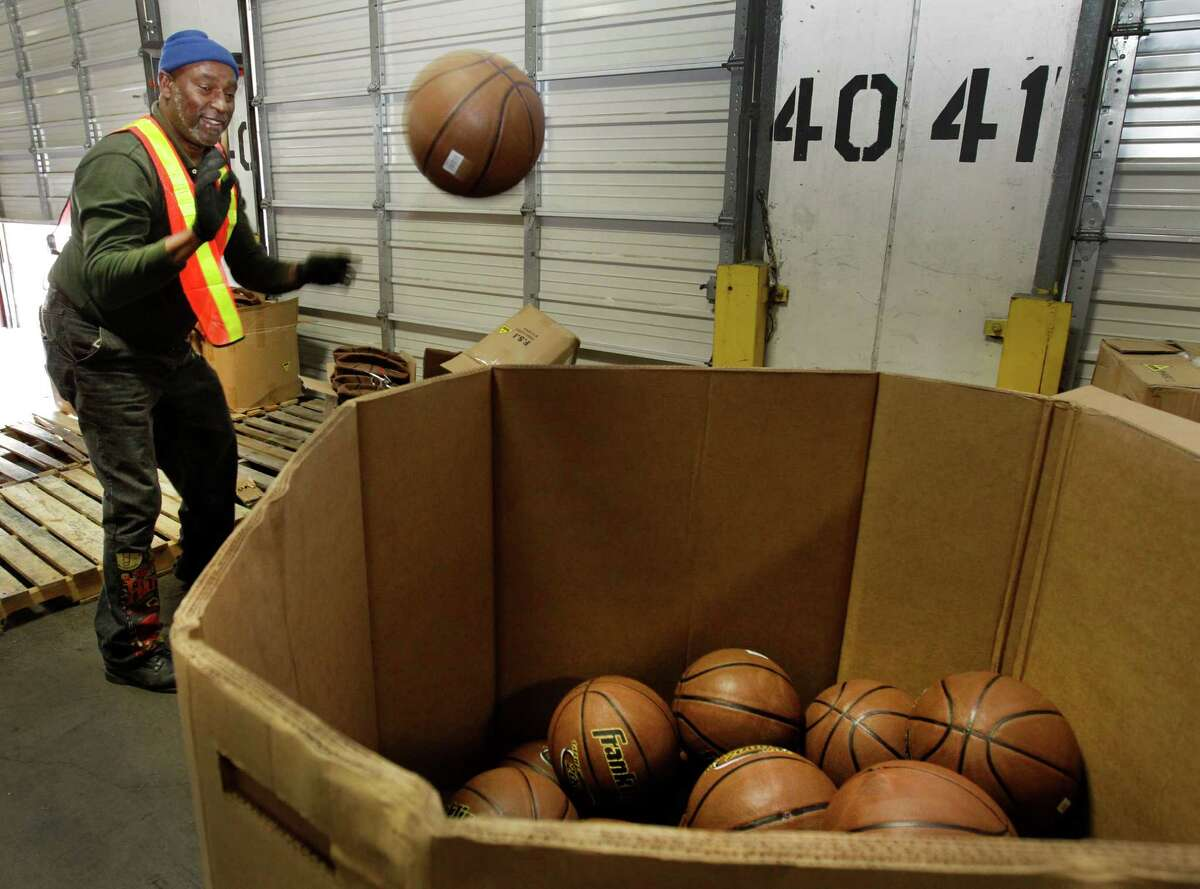 Richard Nickles shows how to put a touch of fun into sorting toys as he tosses a basketball into a bin while working for Goodfellows.