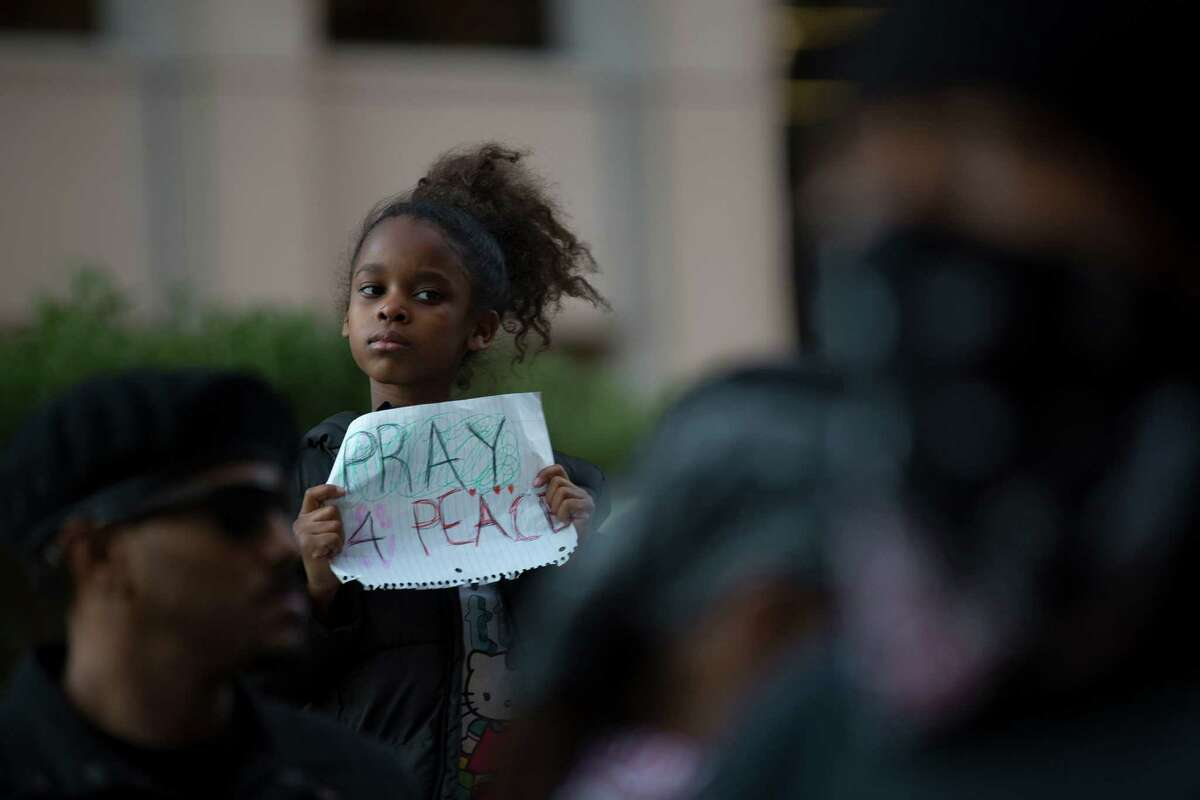 Kennedy Hawkins, 7, holds her sign  at the protest.
