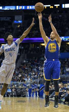 Golden State Warriors guard Stephen Curry (30) puts up a shot in front of Orlando Magic guard Elfrid Payton (4) during the first half of an NBA basketball game in Orlando, Fla., Wednesday, Nov. 26, 2014. (AP Photo/Phelan M. Ebenhack)