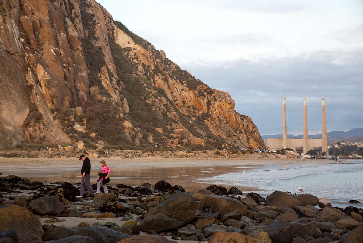 People walk on the shore of Morro Bay with the smokestacks of a former power plant looming in the background. City officials estimated that taking down the stacks could cost $30 million.