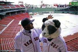CORRECTS TO TARP COVERED, NOT SNOW COVERED - Newly acquired Boston Red Sox free agent third baseman Pablo Sandoval, nicknamed Kung Fu Panda, converses with a person dressed as a panda bear wearing a Red Sox jersey, overlooking a tarp covered Fenway Park field Tuesday, Nov. 25, 2014 in Boston. (AP Photo/Stephan Savoia)