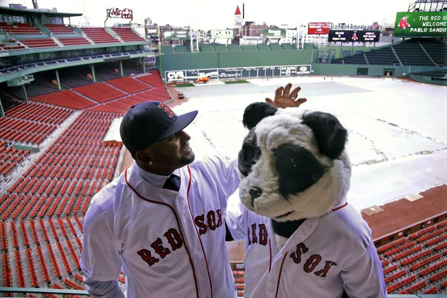 CORRECTS TO TARP COVERED, NOT SNOW COVERED - Newly acquired Boston Red Sox free agent third baseman Pablo Sandoval, nicknamed Kung Fu Panda, converses with a person dressed as a panda bear wearing a Red Sox jersey, overlooking a tarp covered Fenway Park field Tuesday, Nov. 25, 2014 in Boston. (AP Photo/Stephan Savoia) Photo: Stephan Savoia / Associated Press / AP