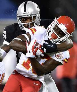 Kansas City Chiefs running back De'Anthony Thomas (13) is wrapped up by Oakland Raiders safety Charles Woodson (24) in the first quarter on Thursday, Nov. 20, 2014, at O.co Coliseum in Oakland, Calif. The Raiders won, 24-20. (John Sleezer/Kansas City Star/TNS)