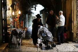 JERUSALEM, ISRAEL - NOVEMBER 26:  A Hasidic man walks by a Muslim merchant in the Old City in Jerusalem on November 26, 2014 in Jerusalem, Israel. Nine Israelis have been killed in a series of stabbings, shootings and hit-and-run attacks in Jerusalem over the past month, unsettling the ancient city of Jerusalem where Jews, Christians and Muslims have lived side by side for thousands of years. The tension and violence on the streets of the city is threatening to further isolate communities and to encourage extremist politicians to exploit the situation.  (Photo by Spencer Platt/Getty Images) *** BESTPIX ***