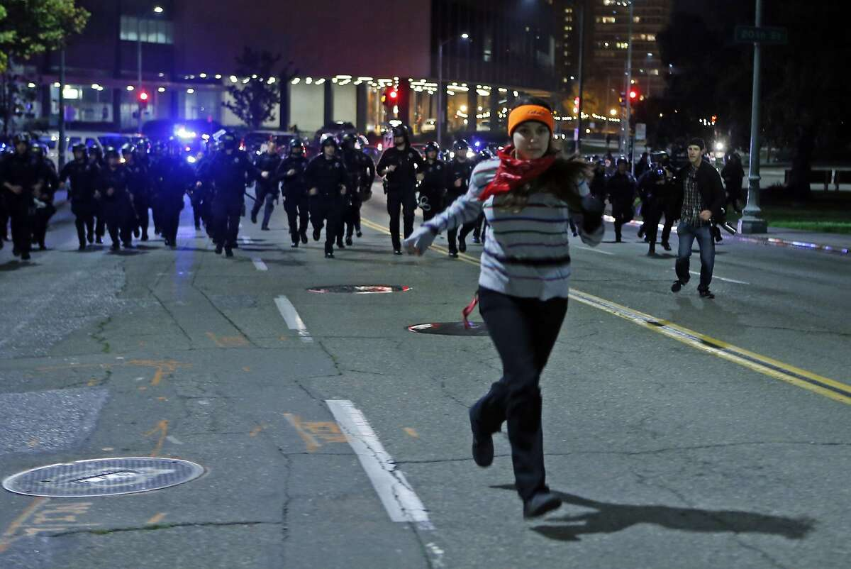 Nava Tiller of Oakland is chased by Oakland Police officers during Ferguson related protests in Oakland, Calif., on Wednesday, November 26, 2014.