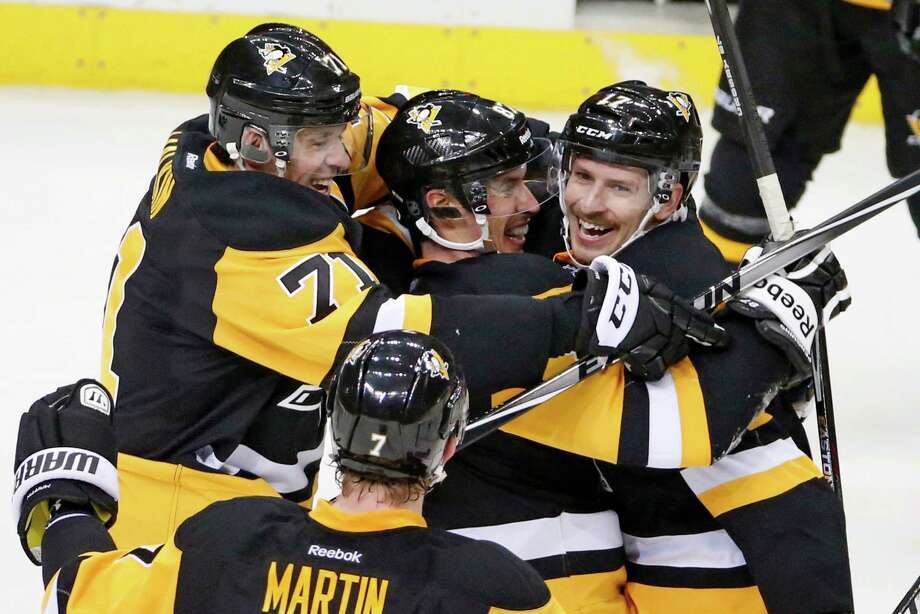 Pittsburgh Penguins' Blake Comeau (17)  celebrates his third goal of the game with Sidney Crosby, center, and Evgeni Malkin (71) during the overtime period of an NHL hockey game against the Toronto Maple Leafs in Pittsburgh Wednesday, Nov. 26, 2014. The Penguins won 4-3 in overtime. (AP Photo/Gene J. Puskar) Photo: Gene J. Puskar / Associated Press / AP