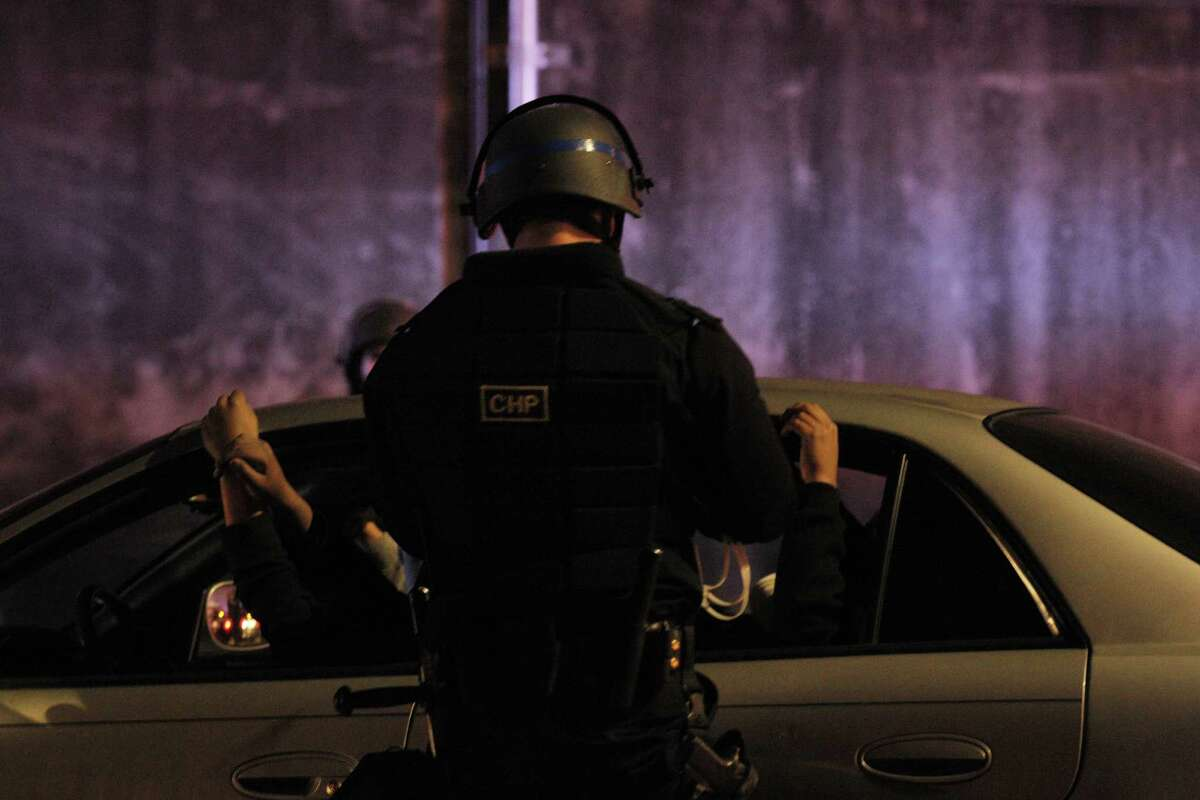 A driver and his passengers hold their hands up while they wait to be processed for citation and released on Wednesday, November 26, 2014, after CHP, Oakland Police and Alameda County Sheriff's officers raided a large sideshow event on Maritime Street in Oakland, Calif. Over 100 vehicles were trapped when law enforcement blocked both ends of the street, preventing almost everyone participating to be caught.