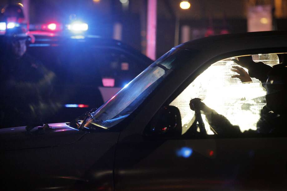A driver keeps his hands on the wheel as his passenger holds his hands up while they wait to be processed for citation and released on Wednesday, November 26, 2014, after CHP, Oakland Police and Alameda County Sheriff's officers raided a large sideshow event on Maritime Street in Oakland, Calif. Over 100 vehicles were trapped when law enforcement blocked both ends of the street, preventing almost everyone participating to be caught. Photo: Carlos Avila Gonzalez, The Chronicle