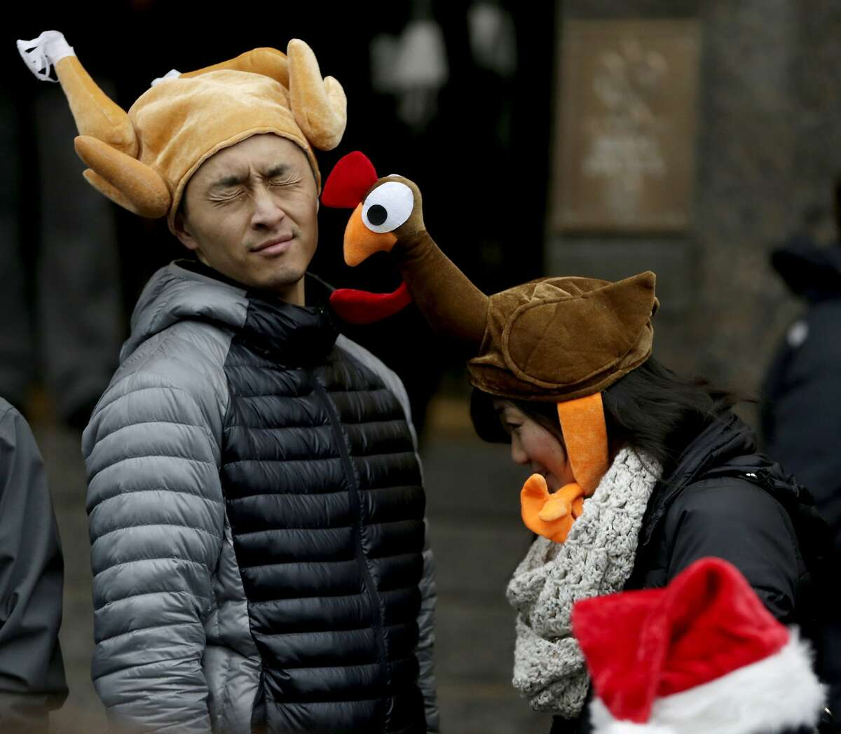 Tamari Hedani, right, hits her boyfriend, Chris Chu, both from San Francisco, with her turkey hat prior to the start of the Macy's Thanksgiving Day Parade, Thursday, Nov. 27, 2014, in New York.