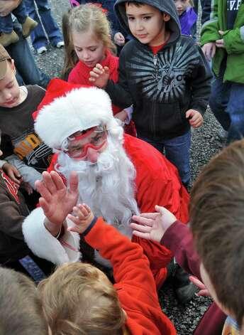 Santa Claus greets children after parachuting into the Ellms Christmas Tree farm in Charlton Saturday Nov. 26, 2011.   (John Carl D'Annibale / Times Union archive) Photo: John Carl D'Annibale / 00015520A