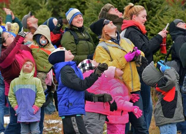 Families watch as Santa parachutes in to the Ellms  Christmas Tree Farm Saturday Nov. 30, 2013, in Ballston Spa, NY.  (John Carl D'Annibale / Times Union archive) Photo: John Carl D'Annibale / 00024698A