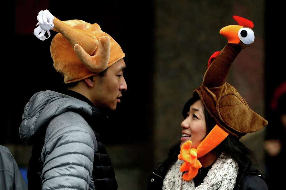 Tamari Hedani, right, and her boyfriend, Chris Chu, both from San Francisco, wear turkey hats prior to the start of the Macy's Thanksgiving Day Parade, Thursday, Nov. 27, 2014, in New York. Photo: Julio Cortez, AP / AP