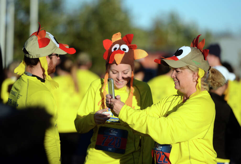 Trey Babino, left, and Cara Shrontz, center, wait while Laurel Shrontz takes a selfie before Thursday morning's Turkey Trot. The Sea Rim Striders hosted the Triangle Therapeutics Turkey Trot 5K, 10K and Kids K at the Event Centre on Thursday morning. The races attracted a little over 1,500 participants. Photo taken Thursday 11/27/14 Jake Daniels/The Enterprise Photo: Jake Daniels / ©2014 The Beaumont Enterprise/Jake Daniels