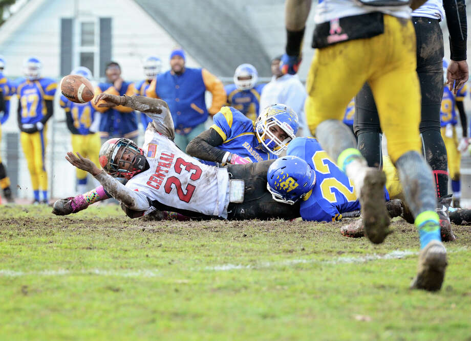 Bridgeport Central's quarterback Mykel Morris (23) loses control of the ball as he is sacked by Harding High School during the Thanksgiving day football game at Hedges Stadium in Bridgeport on Thursday, Nov. 27, 2014. Photo: Amy Mortensen / Connecticut Post Freelance