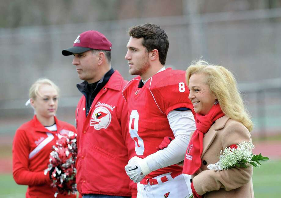 At center, Jack Weigold (#11) of Greenwich with his parents, John Weigold and Mary O'Connor, before the start of the Thanksgiving Day high school football game between Greenwich High School and Staples High School at Greenwich, Conn., Thursday, Nov. 27, 2014. Staples defeated Greenwich by a score of 38-21. Photo: Bob Luckey / Greenwich Time