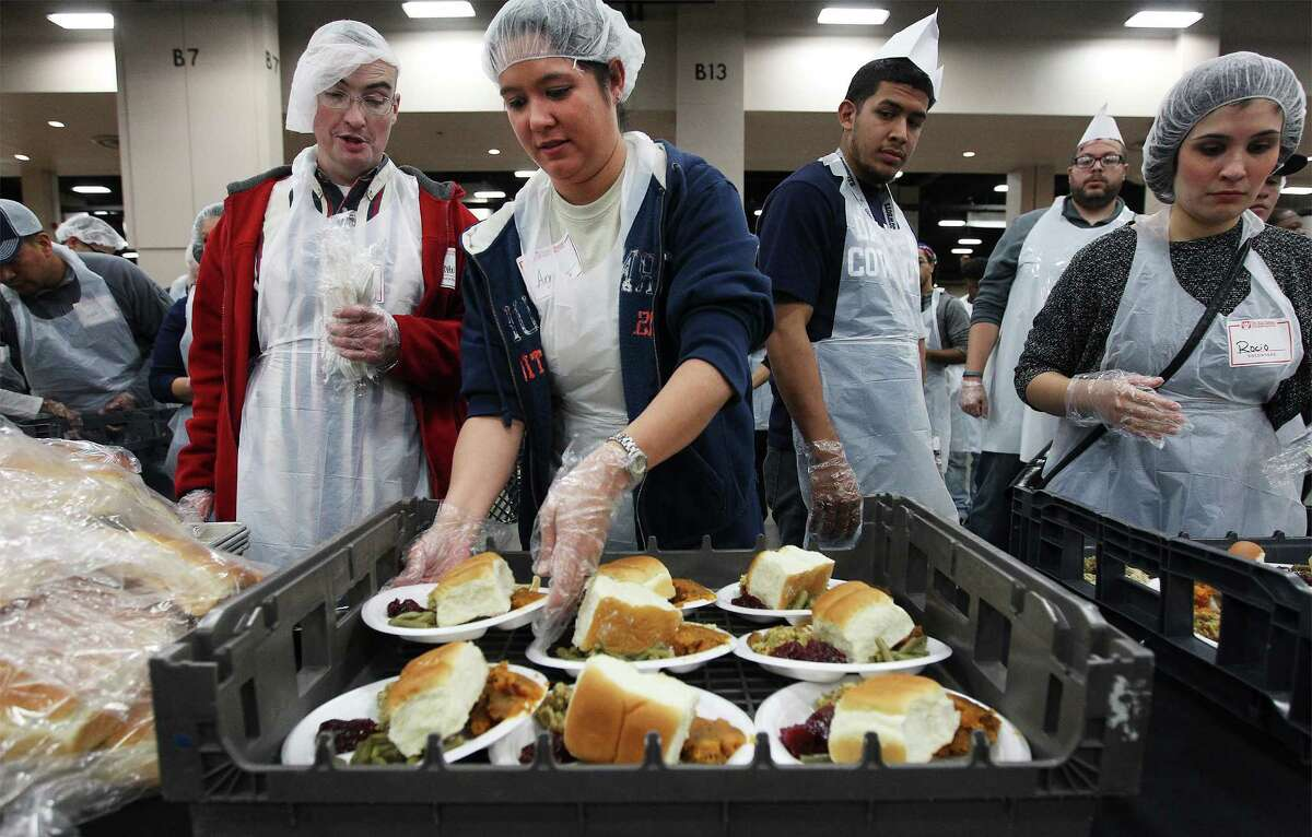 Ana Coker puts plates of food on a serving tray during the 35th Annual Raul Jimenez Thanksgiving Dinner at the Convention Center on Thursday, Nov. 27, 2014. Each year about 25,000 guests gather for a Thanksgiving meal hosted by Patricia Jimenez who has overseen the event since the passing of her father who started the charitable event 35 years ago. About 9,400 pounds of turkey, 6,250 pounds of stuffing and green beans, 4,688 pounds of cranberry sauce and yams, 32, 000 rolls, 650 pounds of gravy and 3,000 pumpkin pies were served. The warm meal fills the heart and stomaches of many in San Antonio who may not have the ability to make do. Over 4,000 volunteers come out every year to help at the event. The remainder of the food will be donated to Daily Bread Ministries according to officials.