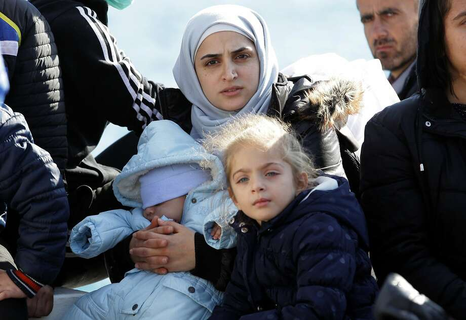 """TOPSHOTS A woman with two children sits on a boat carrying migrants upon their arrival at the Cretan port of Ierapetra on November 27, 2014. Around 700 migrants aboard a freighter that had been drifting in the Aegean Sea for two days began disembarking on the Greek island of Crete, local officials said. The migrants from Syria, Afghanistan, Iran and Iraq, include """"a lot of women and children"""", said Theodosis Kalantzakis, the mayor of Ierapetra. AFP PHOTO / COSTAS METAXAKISCostas Metaxakis/AFP/Getty Images Photo: Costas Metaxakis, AFP/Getty Images"""